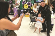 Kim Welch takes a photo of her daughter, Lyric, with Canton Police Officer Louis Salas.
