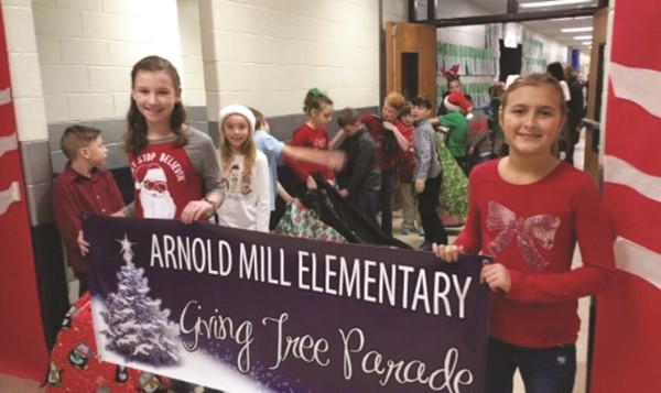 Arnold Mill Elementary School continued its annual Giving Tree program, through which students and staff collect hundreds of gifts and necessities for families in need.  Josie Powers, left, and Kelsey Donnelly lead the parade of students, as they carry their donations through the school.