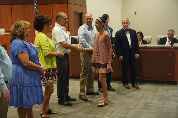 School Board members shake hands with honorees