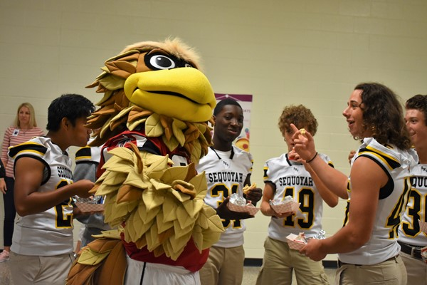 football players eat breakfast with mascot