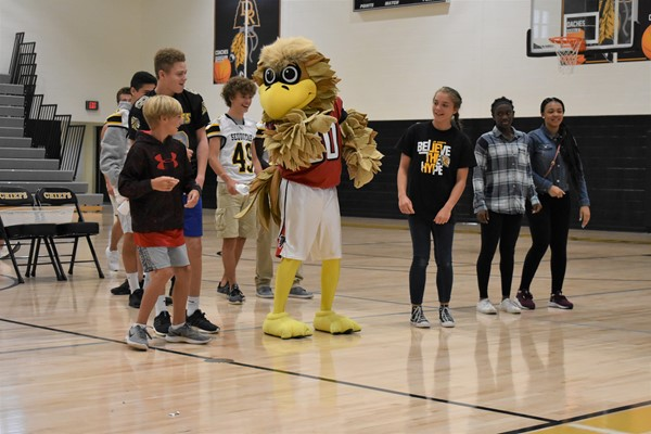 students standing in gym with mascot