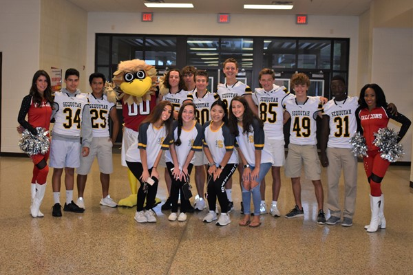 group photo of football players, cheerleaders and mascot