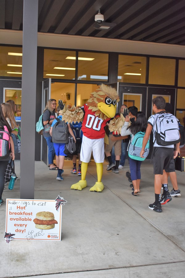 falcon mascot gives high fives to students.