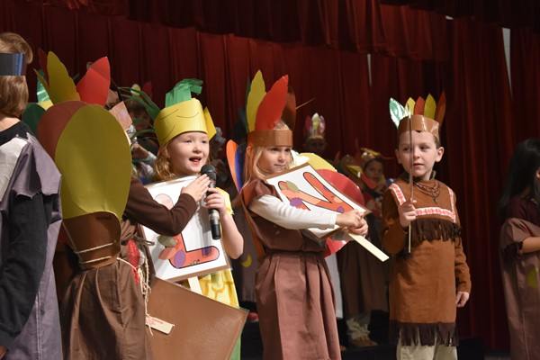 students dressed in thanksgiving costumes (pilgrim, turkey, corn and Indian) singing songs.