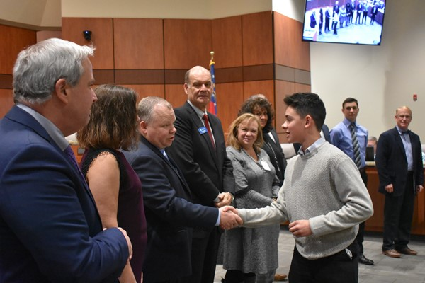 student shakes hands with school board members