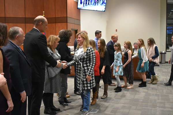 students and teachers shake hands with school board members