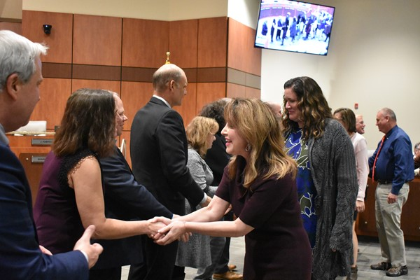 teachers shake hands with school board members