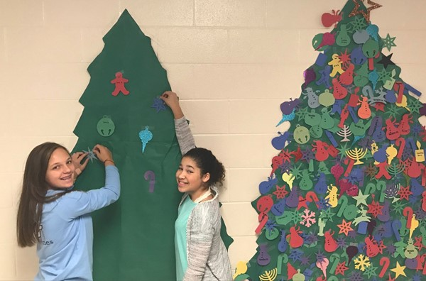 Students throughout E.T. Booth MS are raising money to help families in need this holiday season.  The Lookout Mountain team needed a second tree to track its donations due to students' generosity!  Adding names to the tree are seventh-graders Cara Holland, left, and Chloe Branning.