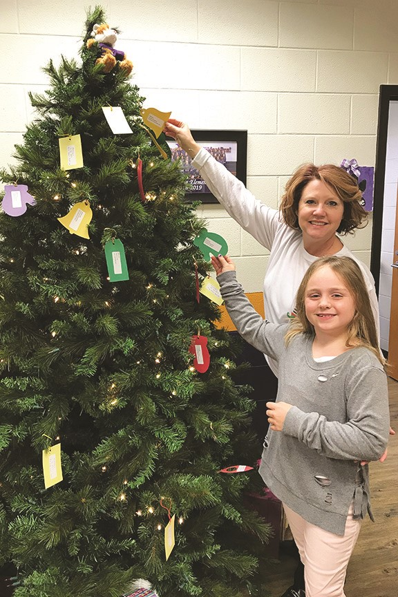 Macedonia Elementary School's Spirit of the Season tree provides opportunities for students to help those less fortunate in the community with needed items, such as: clothing, toys, blankets and cleaning supplies. Macedonia ES Secretary Tracy Smith helps second-grader Anna Peterson pick an ornament from the tree so she can donate the requested items.