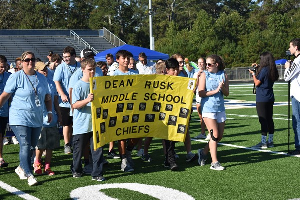 athletes walking with banner