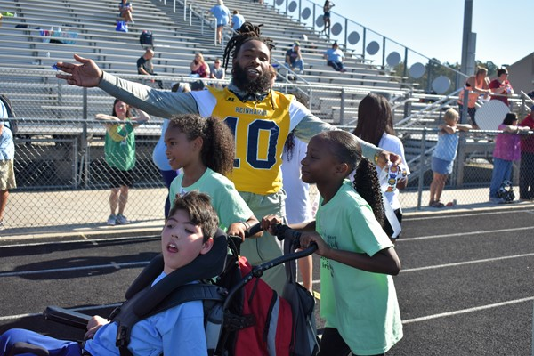 football player cheers as students push athlete in wheelchair