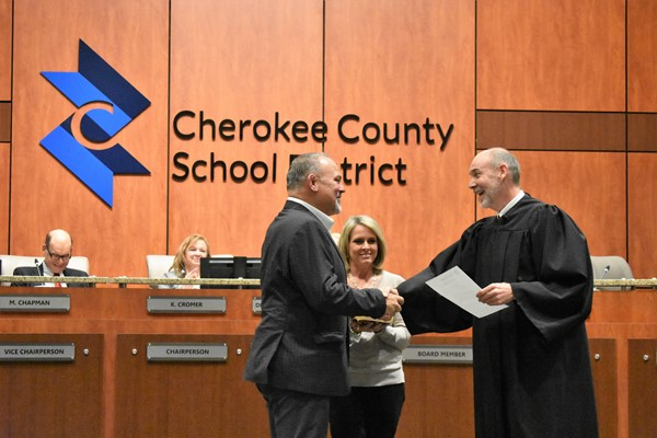 judge reads oath to school board member while family holds Bible
