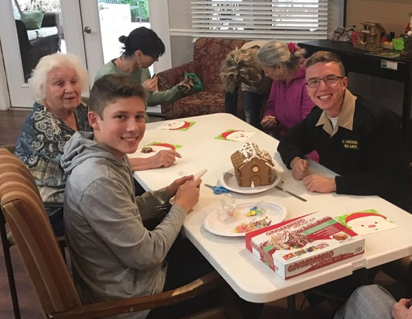 The Woodstock High School cross-country team visited Brookdale Assisted Living for a day of service including holiday decorating and making gingerbread houses with residents.  Triston Leonardi, left, and Rodrick Longshore, who also is a Navy Junior ROTC cadet, volunteer.