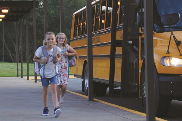 Clayton es fourth-graders Ayla Booth and Elizabeth Chadwick arrive for the first day.
