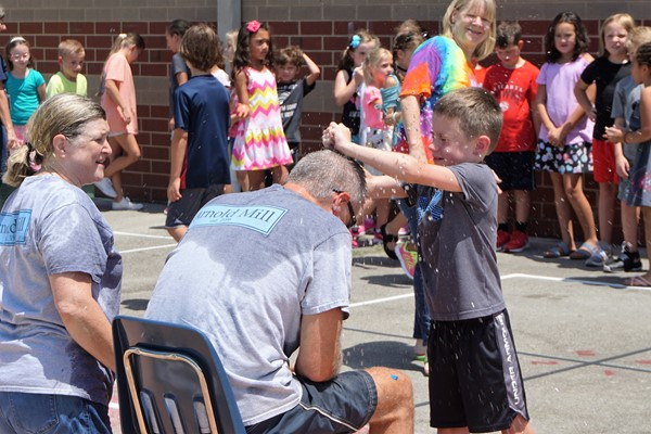 kids throwing water balloons at principal