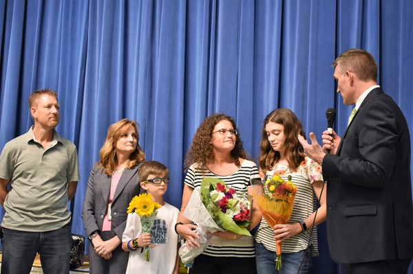 man presents flowers to honoree, surrounded by her family.