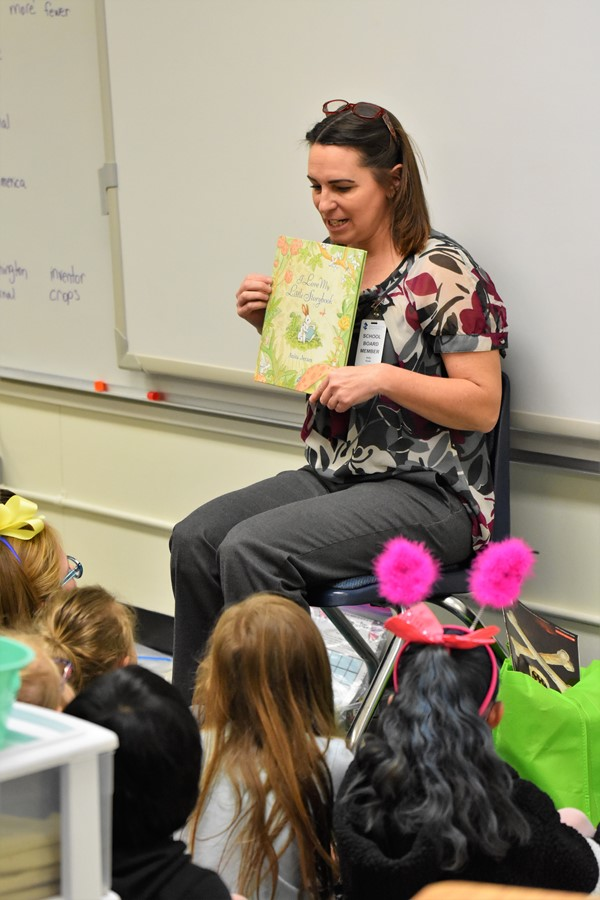 woman reads a story book and shows illustrations to students