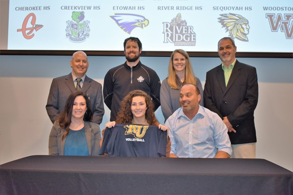 student signing with family and coach