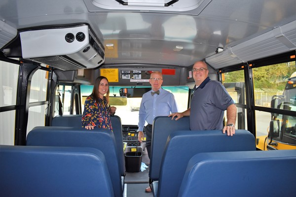 three people standing inside school bus.