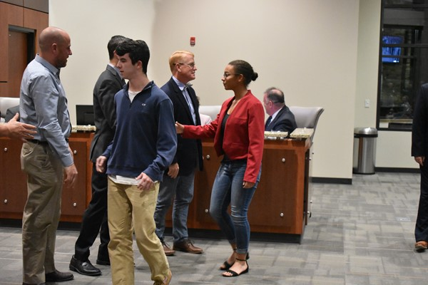 students shaking hands with school board members
