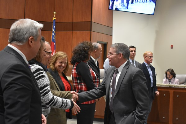 employees shaking hands with school board members
