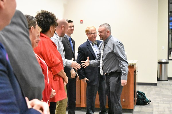 man shakes hand with school board members