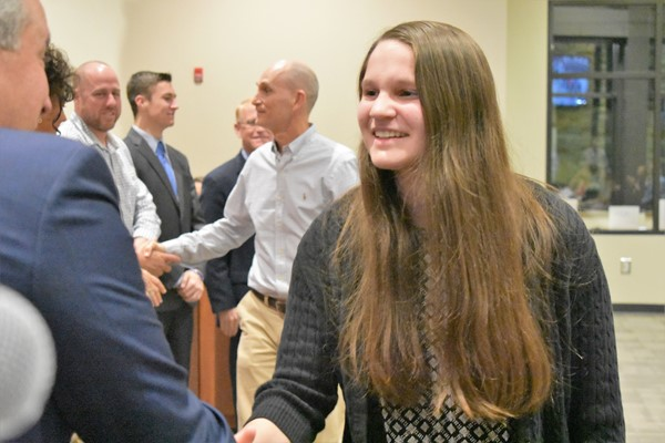 girl shakes hands with school board members