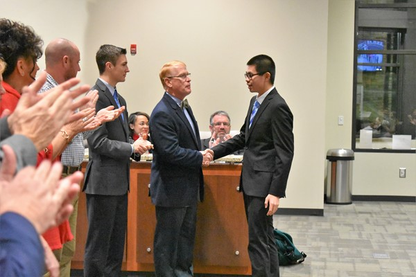 young man shakes hands with school board members