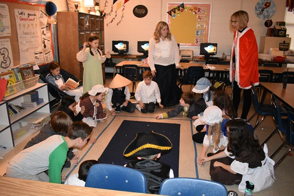 students dressed as colonial Americans engage in classroom activities- rolling marbles on a carpet