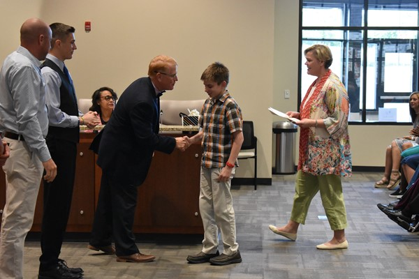 student being congratulated by school board