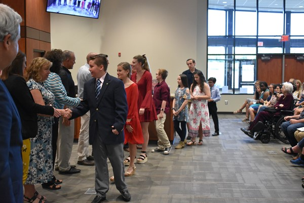 students being congratulated by school board
