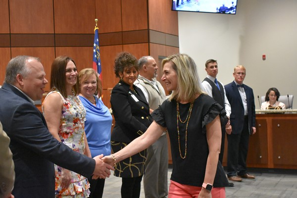 teachers being congratulated by school board members