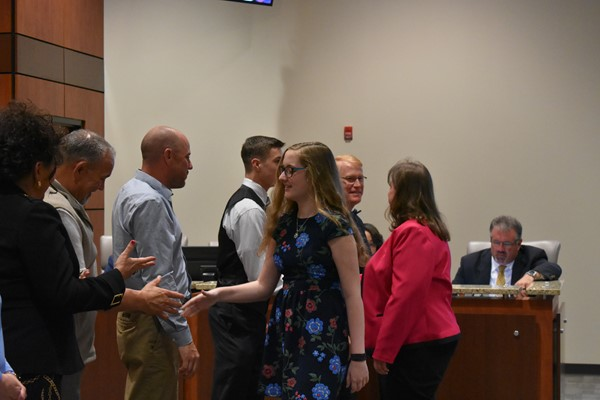 students being congratulated by school board members