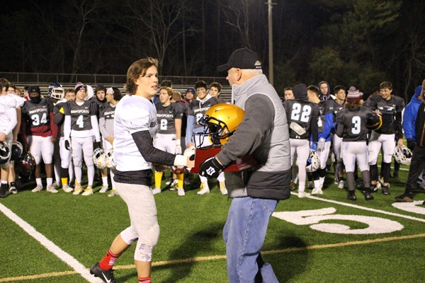 man presents trophy to football player
