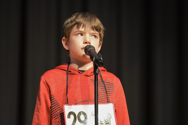 spelling bee participant at microphone