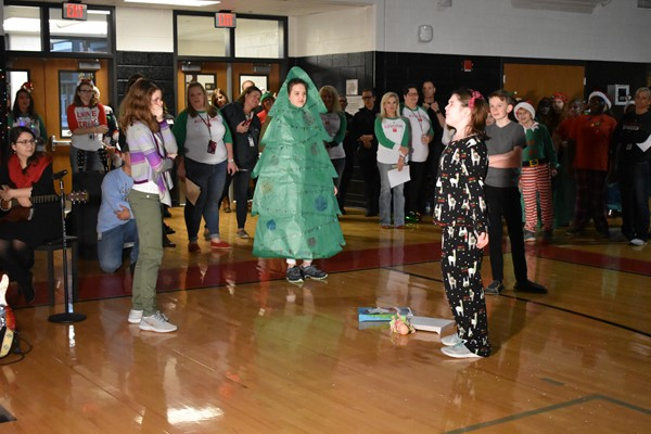 students dressed in pajamas and as a christmas tree performing a play.