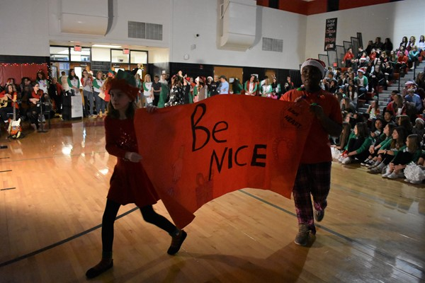 "students holding a sign that reads ""Be Nice."""