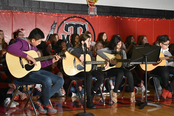 students play guitars, sitting in chairs in a row