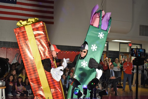 two men dressed as giant gifts sing a song.