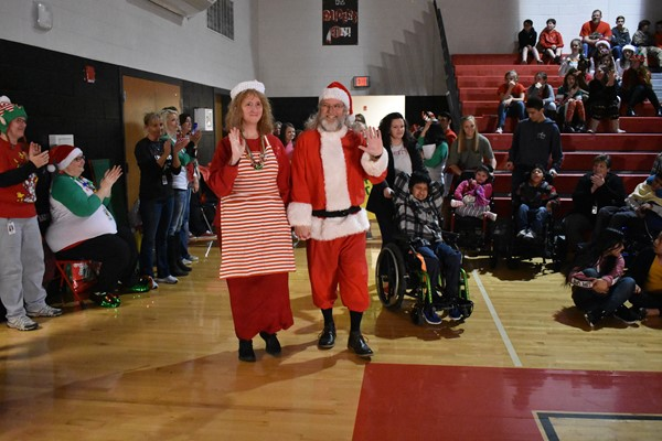 Santa Claus and Mrs. Claus enter the gym