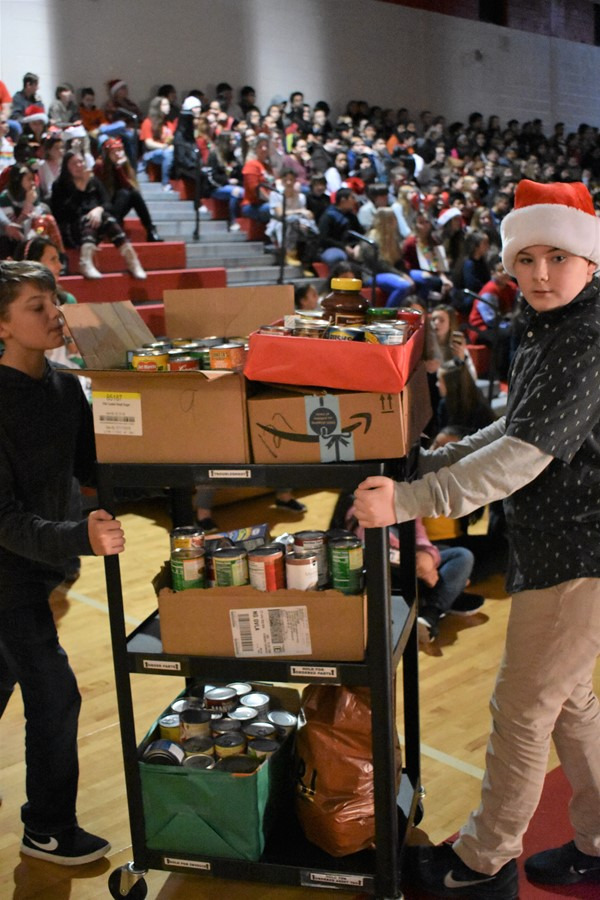 student rolls cart of donations out