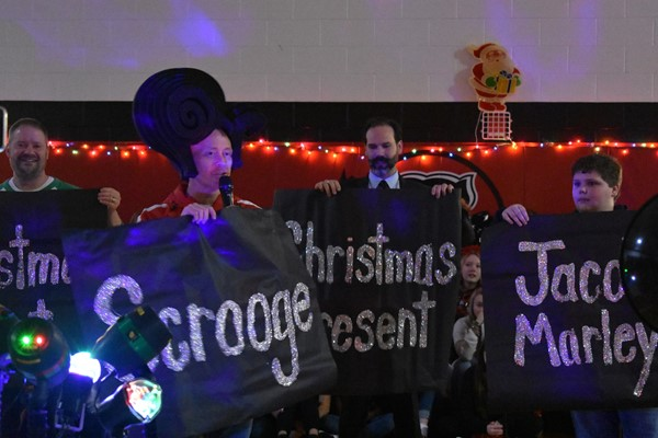"Administrators stand with signs reading ""Christmas Past"" , ""Christmas Present"" and Christmas Future."""