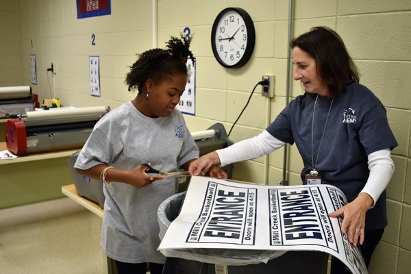 teacher holds poster while student with scissors trims edges.