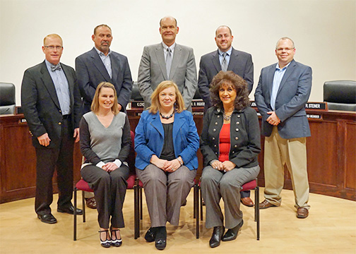 Front row, from left, Kelly Poole, Kyla Cromer and Patsy Jordan. Back row, from left, Superintendent Dr. Brian V. Hightower, Robert Rechsteiner, Mike Chapman, John Harmon and Clark Menard.