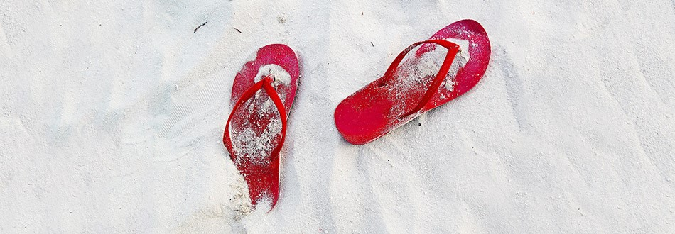red flip flops in white sand