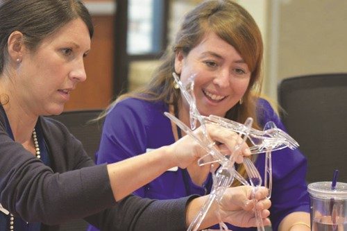 Staci Wiech, left, and Jade Ricketts of Zoo Atlanta work on a STEM challenge at the CCSD and Discovery Education partnership kick-off.  Teams were tasked with quickly building the highest tower possible using a box of plastic silverware.