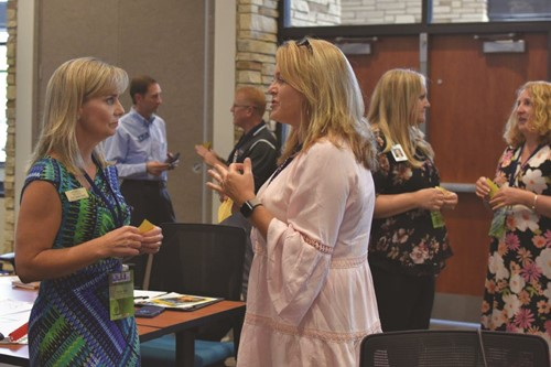 Sandra Jones, left, of Kennesaw State University discusses STEM concepts with Creekland MS teacher Kim Bennett at the CCSD and Discovery Education partnership event.