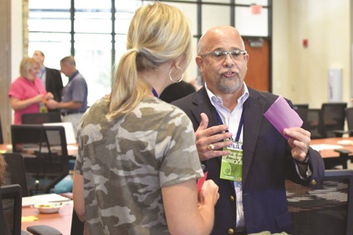 Reinhardt University Associate Provost of Academics Dr. Jacob Harney talks with E.T. Booth MS teacher Kara Reeder during the CCSD and Discovery Education partnership launch.
