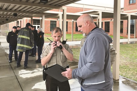 Cherokee High School Principal Todd Miller meets with law enforcement officers as he practices evacuation procedures during the multi-agency emergency response drill on Thursday at Cherokee High School.