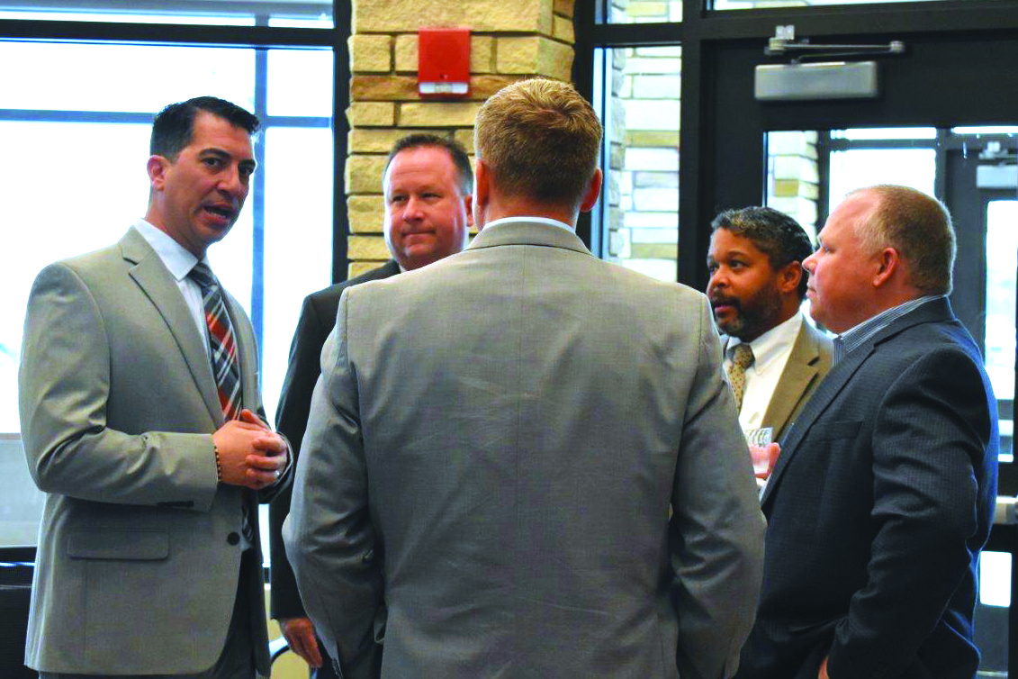 Mike Santoro, who will serve as Principal at Woodstock MS, left, talks with, from left to right, newly named CCSD Supervisor of Facility Support Services Scott Krug, CCSD Chief Information Officer Bobby Blount and School Board member Clark Menard.